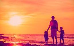 生和走在海滩的两个孩子在日落 免版税库存图片