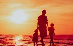 生和走在海滩的两个孩子在日落 免版税库存照片