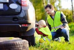 生和他的一起修理汽车和变速轮的小儿子在夏日 库存图片