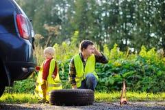 生和他的一起修理汽车和变速轮的小儿子 免版税图库摄影
