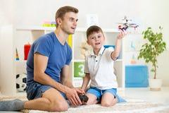 生和他的与RC直升机玩具的儿子戏剧 库存照片