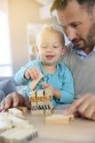 生和他的使用与木块的小儿子 免版税库存图片