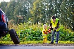 生和他的修理汽车和变速轮的小儿子 图库摄影
