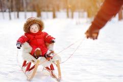 生和他的小孩儿子获得乐趣在冬天公园 库存照片
