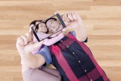 生和他的拍在地板上的孩子照片 库存照片