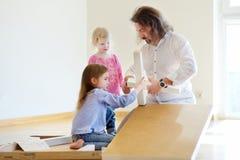 生和他的装配桌的两个女儿 免版税库存图片