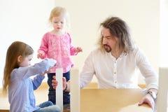 生和他的装配桌的两个女儿 库存图片