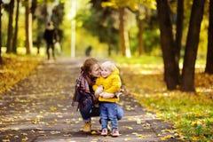 生和他的走在秋天公园的小孩儿子 免版税库存图片