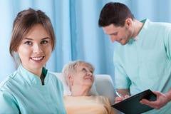 年轻医生和更老的患者 库存照片