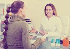 医生咨询的访客妇女在审美中心 图库摄影
