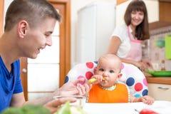 生喂养他的烹调在厨房的婴孩和母亲 免版税库存照片