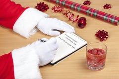 生喝的圣诞节检查他的圣诞老人名单和一杯 免版税库存照片