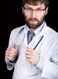 医生在一件白色医疗长袍、身分和藏品听诊器 免版税图库摄影