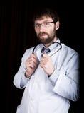 医生在一件白色医疗长袍、身分和藏品听诊器 图库摄影