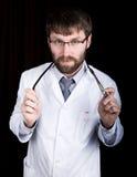 医生在一件白色医疗长袍、身分和藏品听诊器 库存照片