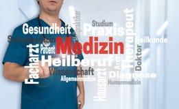 医生在与Medizin的观察者显示在德国医学wordclo 库存图片
