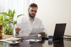 医生在坐在书桌和读病历的办公室 图库摄影