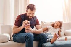 生在家做修脚给逗人喜爱的矮小的女儿 免版税库存图片