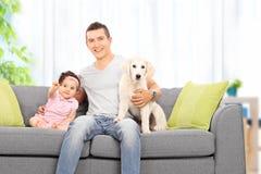 生在家坐与他的女儿和小狗 库存照片