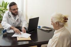 医生在患者的病史显示手指文字 医生解释并且显示患者的结果 免版税库存图片