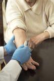 医生在老妇人的静脉投入针 免版税图库摄影