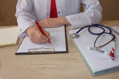 医生在诊所的一个医疗办公室坐并且写病史 医学doctor& x27; s工作表 库存图片