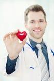 医生在他的手上拿着一个心形的模型 免版税图库摄影