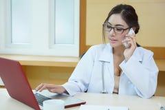 年轻医生妇女讲话由电话机动性在她的办公室 库存照片