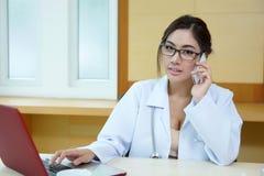 年轻医生妇女讲话由电话机动性在她的办公室 图库摄影