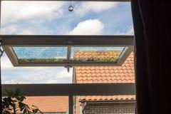 生存都市 从开放UPVC窗口的看法与庭院反射 免版税库存照片