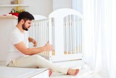 生安装小儿床,为一个新的婴孩做准备在家庭 库存照片