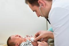 医生审查的哭泣的婴孩 库存照片