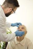 医生审查眼睛,结膜非常老妇人在测试期间的医生老年医学专家 免版税库存图片