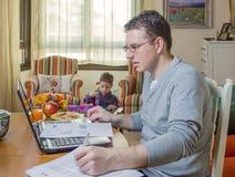 生工作在家庭办公室和儿子使用 图库摄影