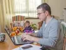 生工作在家庭办公室和儿子使用 库存照片