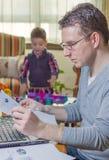生工作在家庭办公室和儿子使用 免版税库存图片