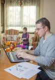 生工作在家庭办公室和儿子使用 免版税库存照片
