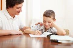 生帮助的家庭作业儿子 免版税库存照片