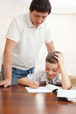生帮助的家庭作业儿子 免版税图库摄影