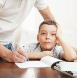 生帮助的家庭作业儿子 免版税库存图片