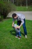 生帮助他的第一步的儿子 库存照片