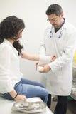 医生弯曲的妇女的手 免版税库存照片