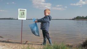 生态污染废物本质上,孩子男孩画象有垃圾袋的在手中在清扫塑料垃圾以后 股票录像