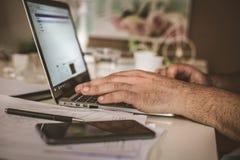 生意人他的膝上型计算机运作的年轻人 焦点在手边 免版税库存照片