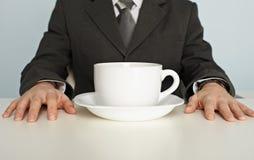 生意人咖啡杯巨大的最近的表 库存照片