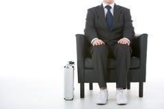 生意人坐的运动鞋佩带 库存照片