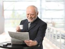 生意人愉快的报纸读取 免版税库存图片