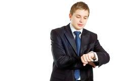 生意人检查英俊他的手表腕子 免版税库存图片