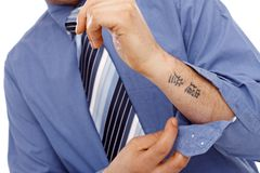 生意人的身体局部与纹身花刺的在前臂 免版税库存图片