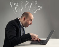 生意人看起来他的膝上型计算机惊奇 免版税库存图片